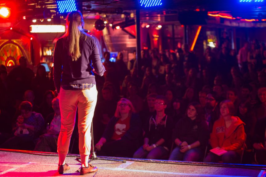 A person stands on a stage in front of a microphone. Their back is to us, they are facing an audience. The room is dimly lit with red- and blue-toned lights.