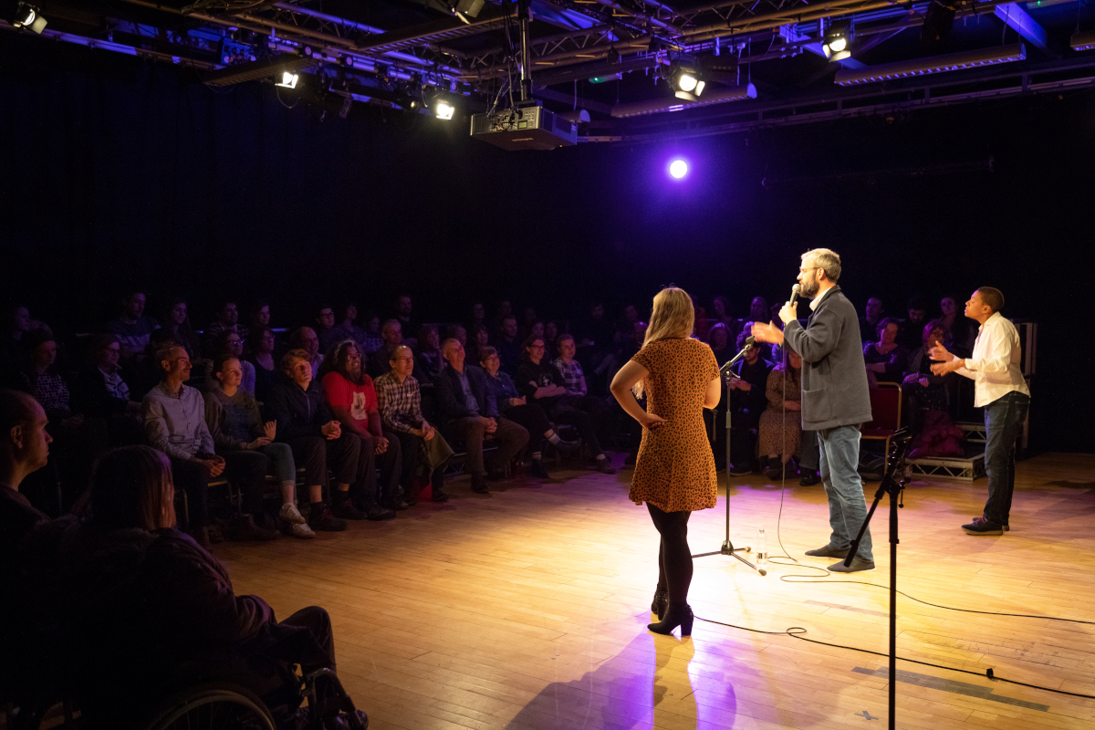 Three people stand in the middle of a performance space. The person in the middle speaks into a microphone. An audience watches them.
