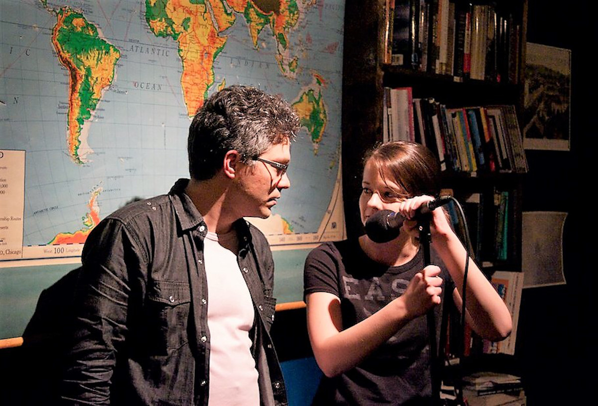Two people turn to look at each other. The person on the right stands behind a microphone and holds onto it. They stand in front of a large world map and a tall bookshelf.