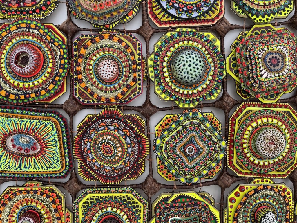 A close-up of Cell Grid (Brown) (2019) by Amie Esslinger. A brown textile grid with 6 columns and 5 rows. Each cell in the grid is occupied by an ovoid body resembling a biological cell. These cells have various patterns and colours like green, bright yellow, blue, red, orange. Some are shaped like flowers, some are square with the corners cut off, some are combinations of both shapes, with multiple layers. The grid frame lines extend beyond the frame of the grid holding all the cells, and the bottom has long threads flowing down like a fringe (same material as the brown grid). This close-up shows 3D layering incorporated into the work.