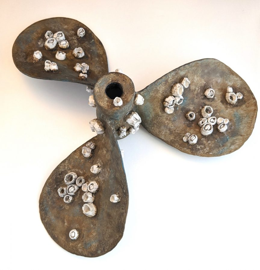 Rusted boat propeller with small barnacles growing on it