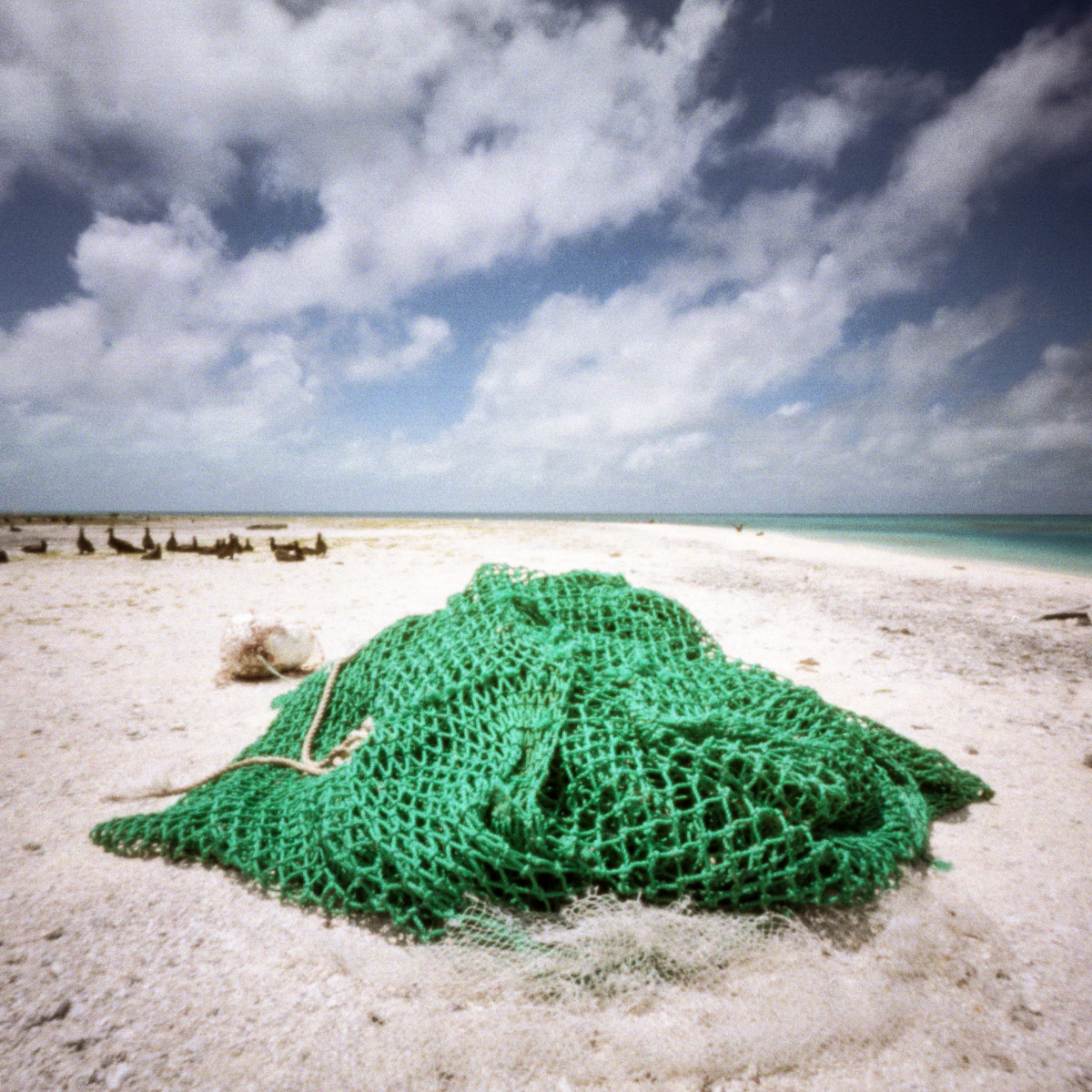 A photo of a large green fishing net in a heap on the beach.