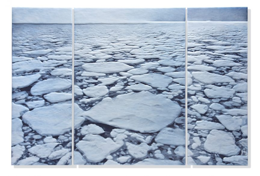 Many pieces of ice floating on a large body of water in shades of blue and white.