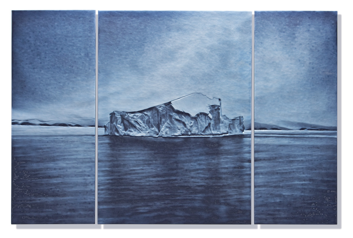 An iceberg on a still body of water and big sky in shades of blue and white.
