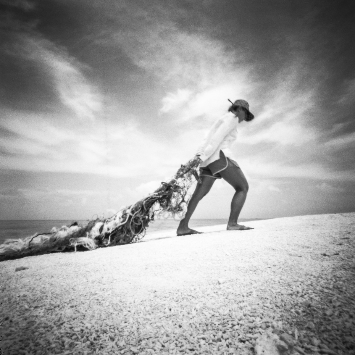 A black and white photo of a woman dragging behind her a large amount of marine debris.