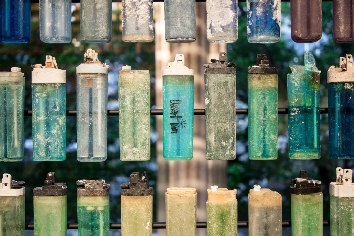 A close up photo of a row of plastic lighters in various shades of blue and green.