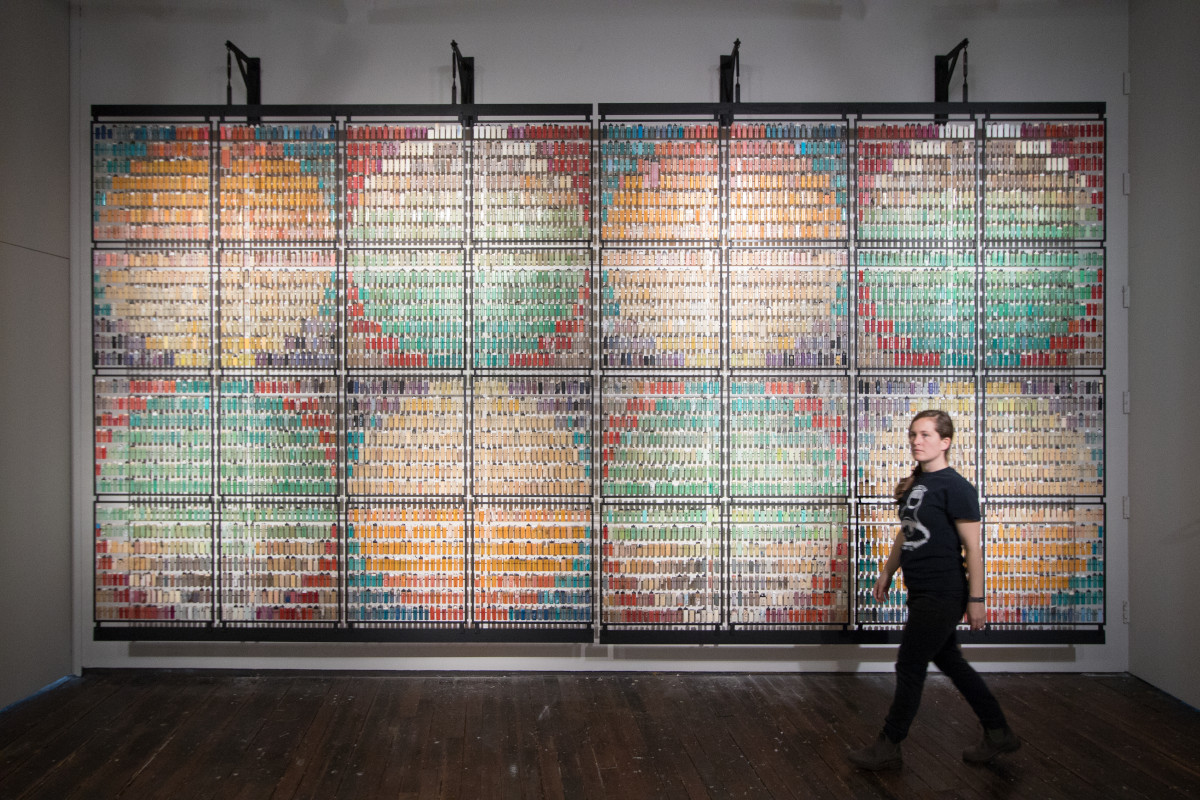 A photo of a large rectangular arrangement composed of lighters. They form eight colourful circles inside eight colourful squares. A woman walks in front of the installation.