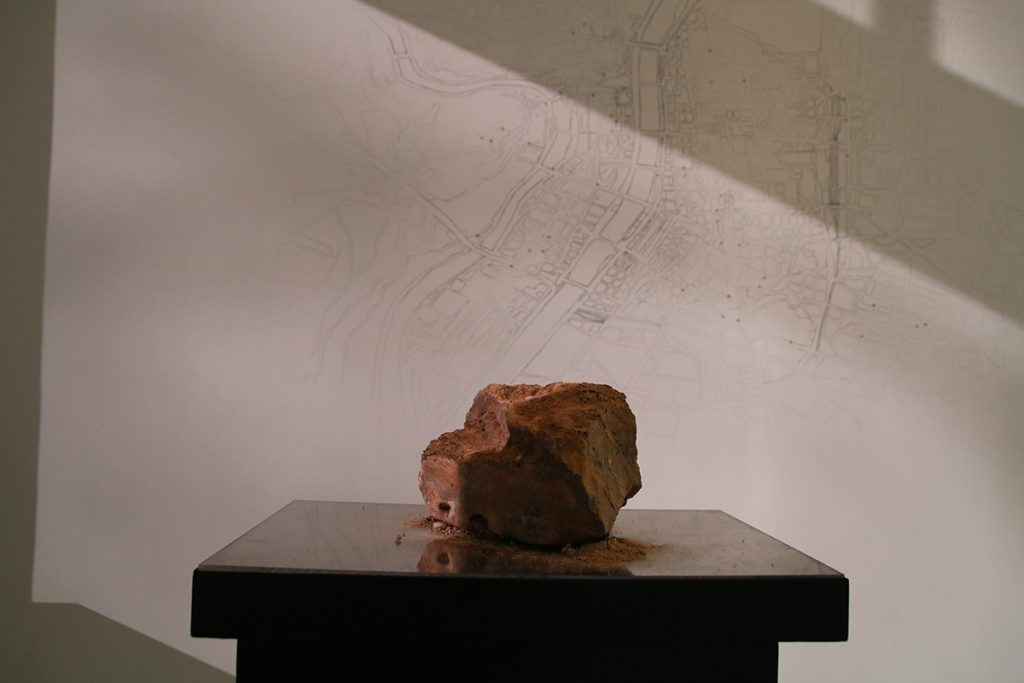 Slab of red clay on a pedestal. Behind it is a black and white illustrated map.