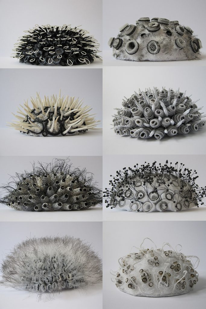 Eight small domes covered in beige, white and black fabrics and other materials that poke outward, like cacti.