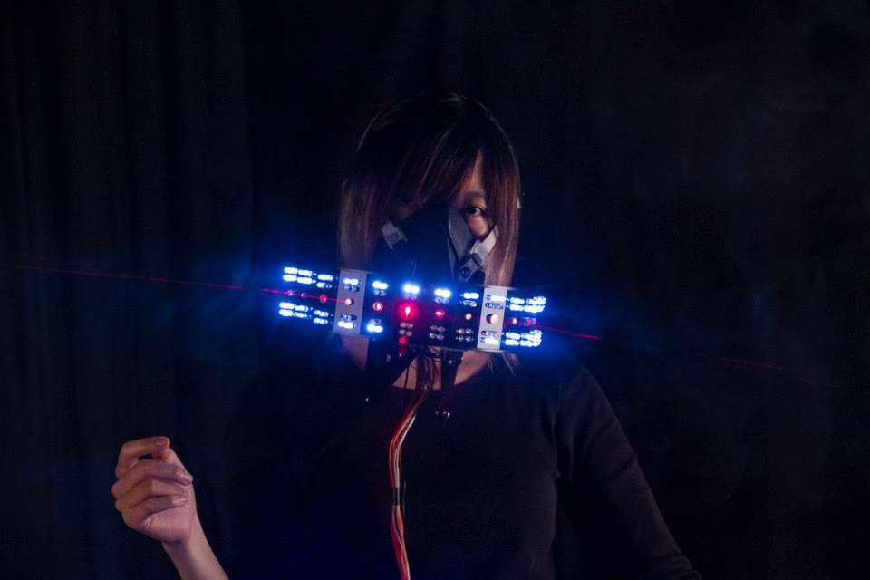 Woman stands in a dark room with a mask covering her mouth and nose. The mask contains tech and projects blue lights.