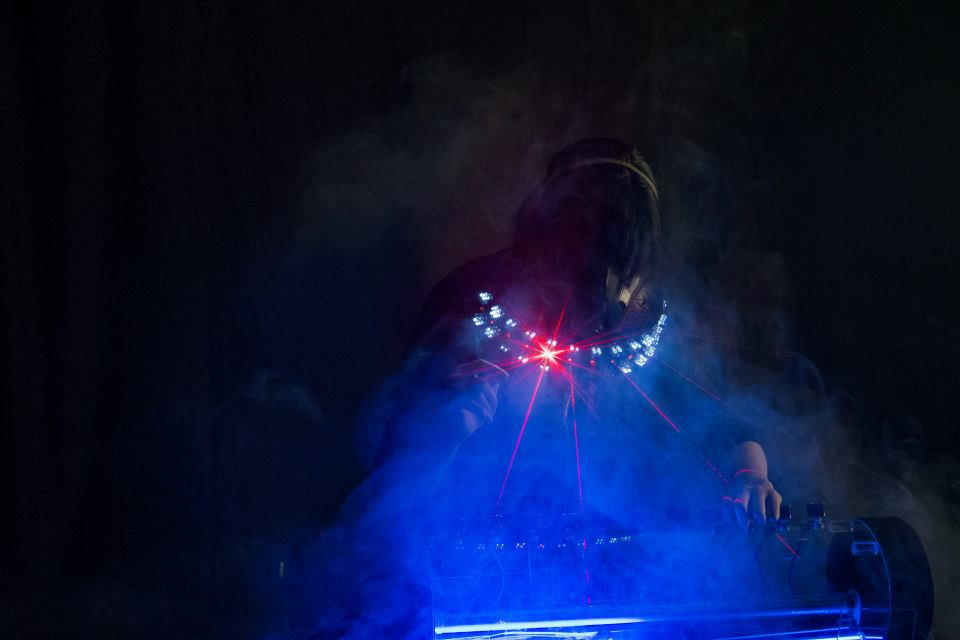 Woman looking downward wearing a mask that projects blue light into fog.