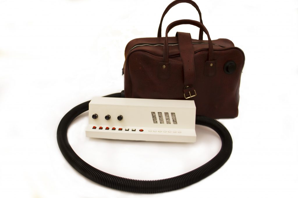 Retro vacuum--a large brown bag with a hose coming out of it. The hose curls into a circle with a white control panel at the other end.