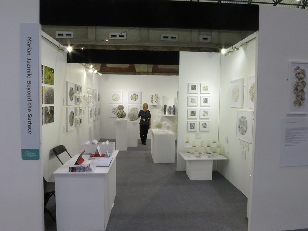 Marian Jazmik stands in the exhibition space with the walls covered by her framed works.