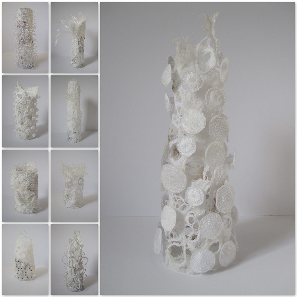 Cylinders with the outside covered in white shapes and textures made of fabric.