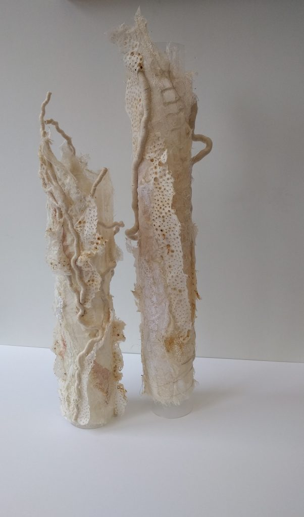 Two cylinders covered in white materials that almost look like corals.