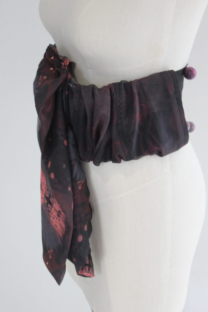 A photo of a mannequin with a large swathe of dark gathered fabric wrapped around its waist.