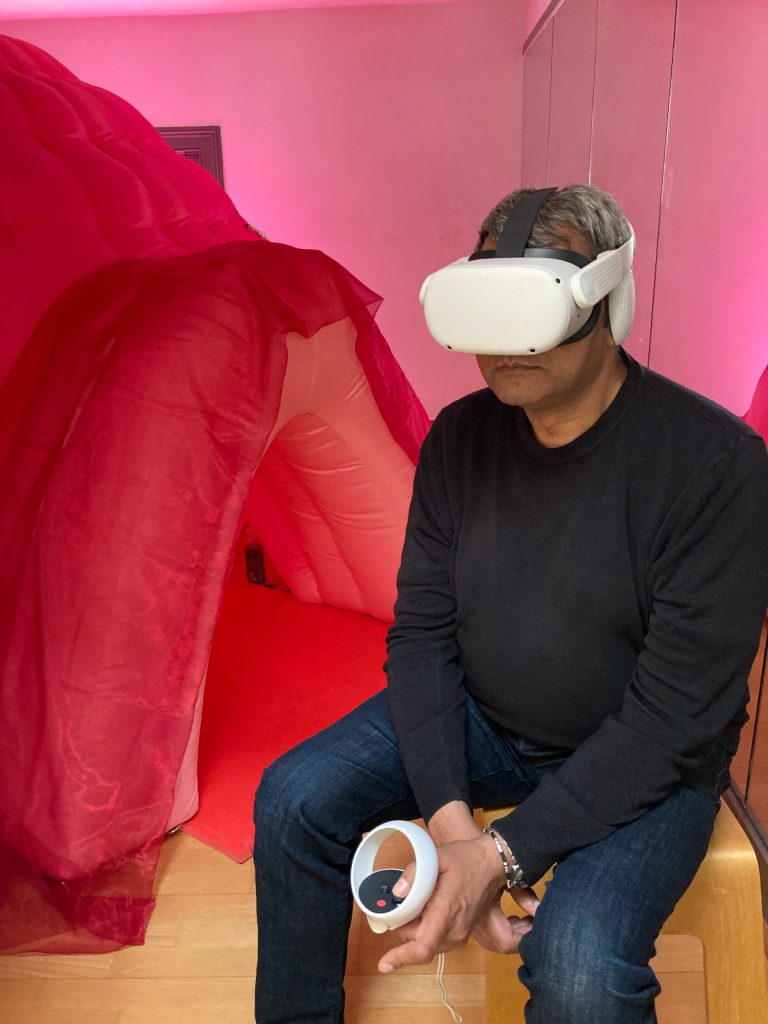A photo of a man sitting on a stool. He wears a white headset over his eyes and holds a controller. In the background is the entrance of a large inflatable pink tent.