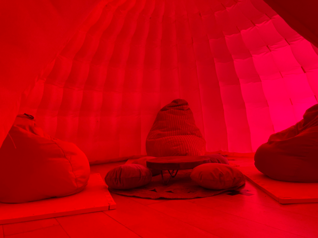 A photo of three bean bag chairs around a small table and small cushions. They sit inside a dark pink dome.