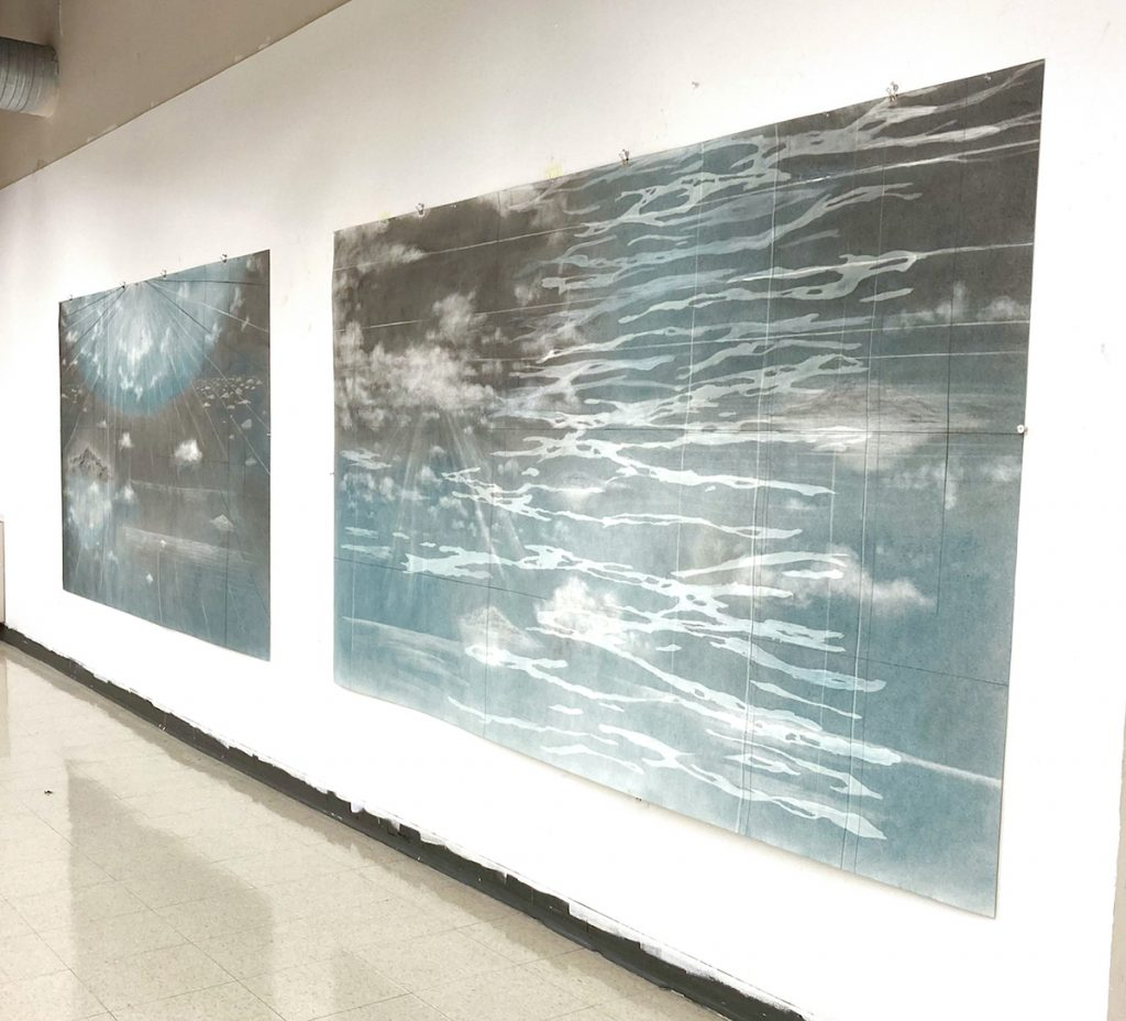 Wall where two drawings of blue and gray ocean currents and clouds are hung.