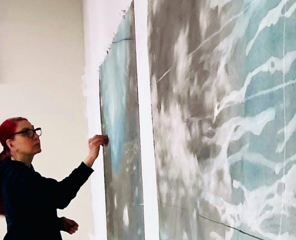 Wall where two drawings of blue and gray ocean currents and clouds are hung. Holly Fay is working on one of these drawings.