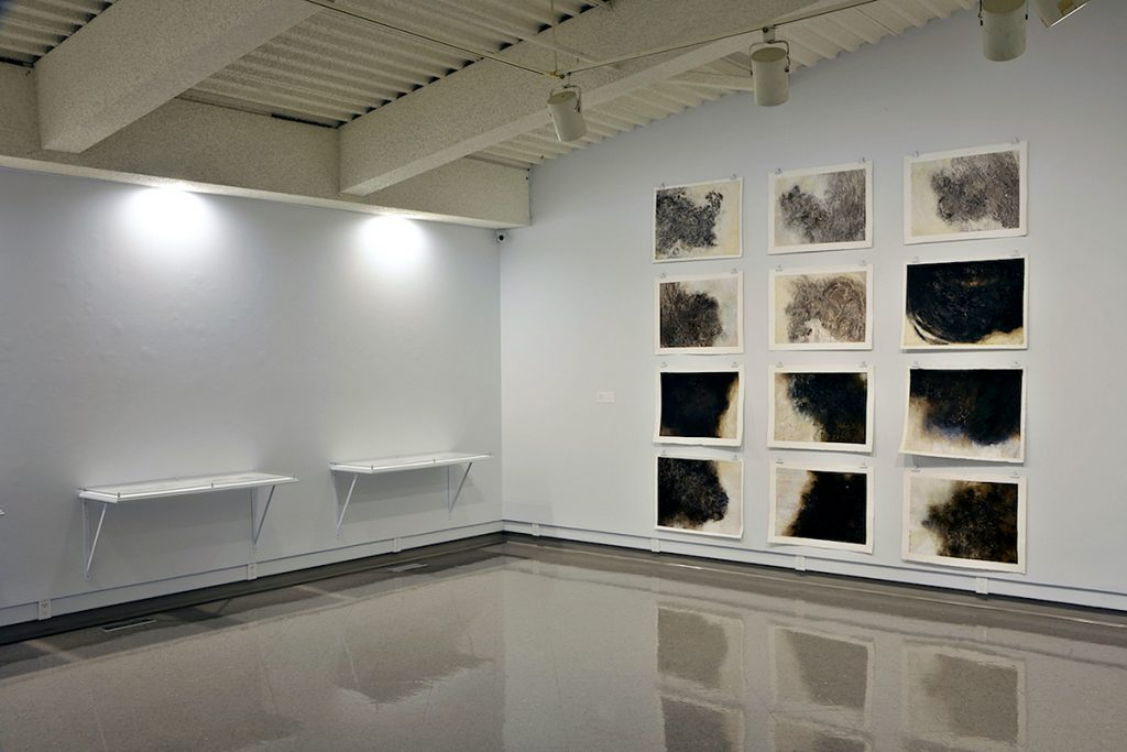 Exhibition space with Holly Fay's illustrations of black clouds hung on one white wall in a 3x4 grid pattern and some lying flat on a shelf on an adjacent wall.