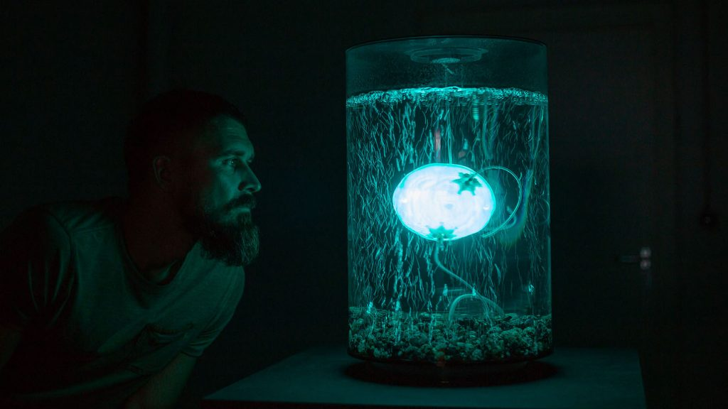 A man in profile looking at glowing orb floating in water in a cylindrical glass container, all bathed in teal-blue light.