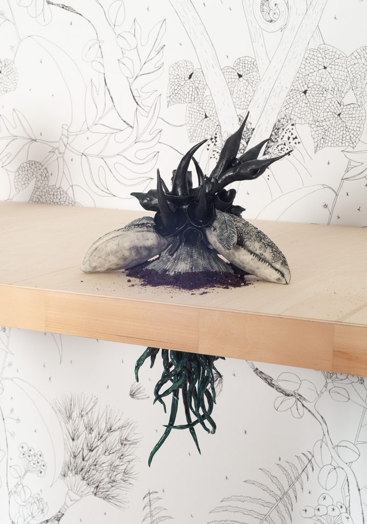 A sculpture of a black spikey plant with a base that looks like lobster claws sits on top of a table. Underneath the table, it's dark green roots are visible.