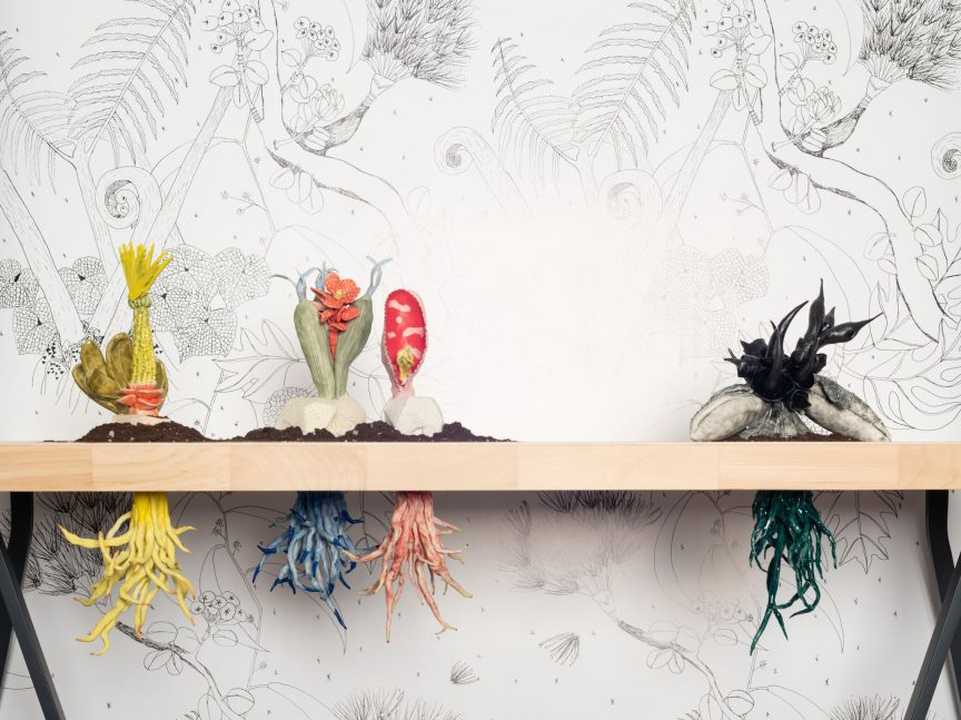 Four colorful sculptures of fictitious plants sit on a wooden table with their equally bright roots below. Behind them is a panel of black and white illustrated plants.