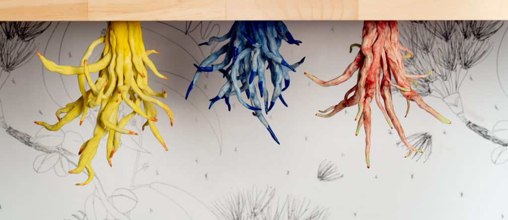 Three sets of sculpted roots -- one yellow, one blue, and one red -- emerging from below a wooden table.
