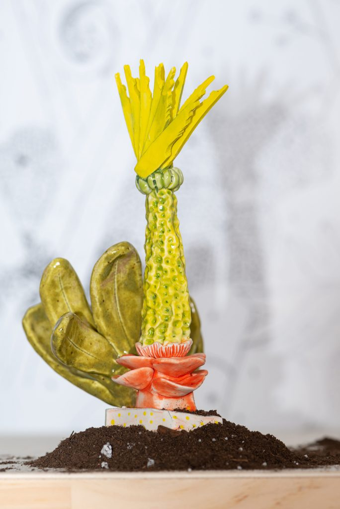 A sculpture of a yellow-green plant that emerges from a pink flower-like base. Coming from the side are large leaves. At the top of the plant are sharp yellow spikes.
