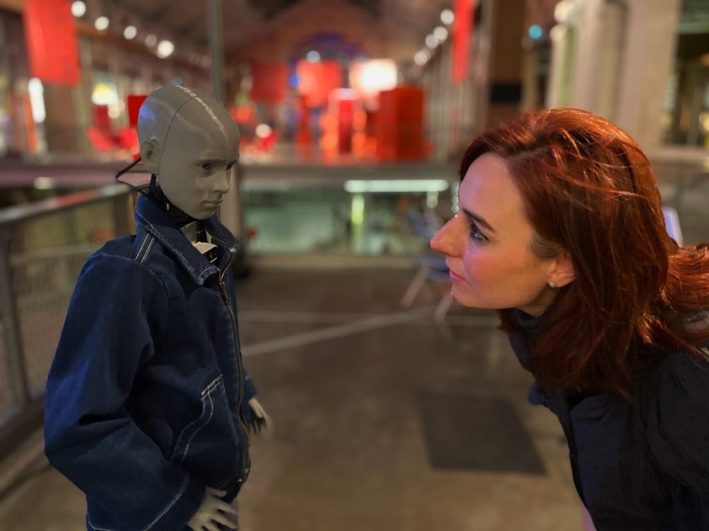 A woman bends down to look eye-level at a childike, humanoid robot wearing a jean jacket.