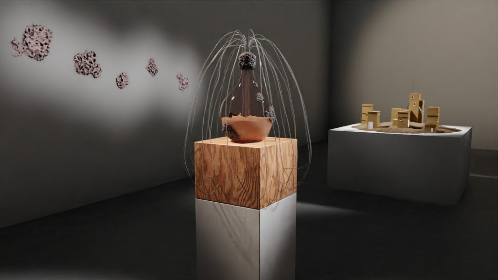 A visualization of the gallery installation featuring a large glass vessel containing a yeast culture, the top of which has numerous tubes inserted into it. The glass vessel sits on a wooden pedestal with objects on the wall in the background.