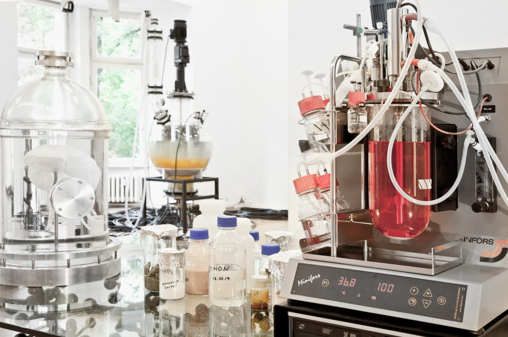 Biochemistry apparatuses with different colored liquids sit on a table in front of a white background.