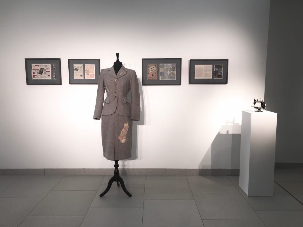 A gallery view of the installation, with a war-time grey women's suit on a dress form and four panels on the wall behind it.