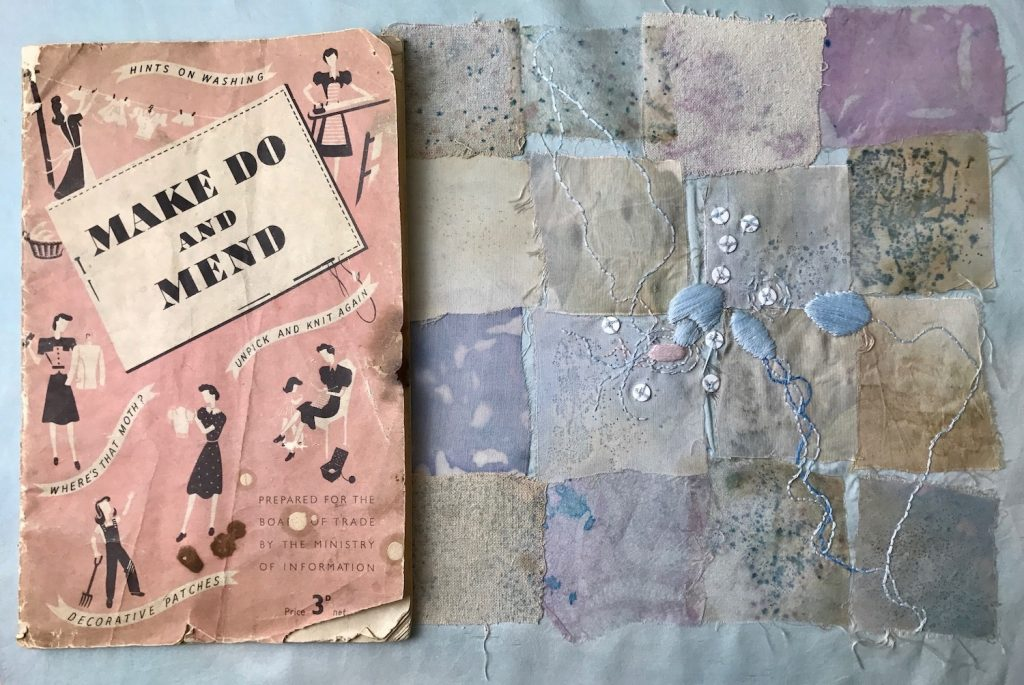 """A pink, weathered, vintage-style booklet with the title """"MAKE DO AND MEND."""" This sits next to a patchwork of dull, pastel-colored squares embroidered with blue and white thread patterns that resemble bacteria."""