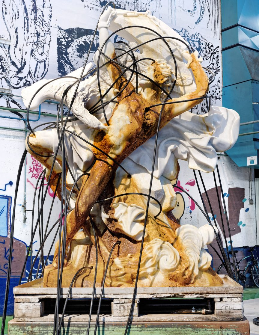 A marble sculpture of the figure of Prometheus, with black cables and copper-colored material spilling down the front.