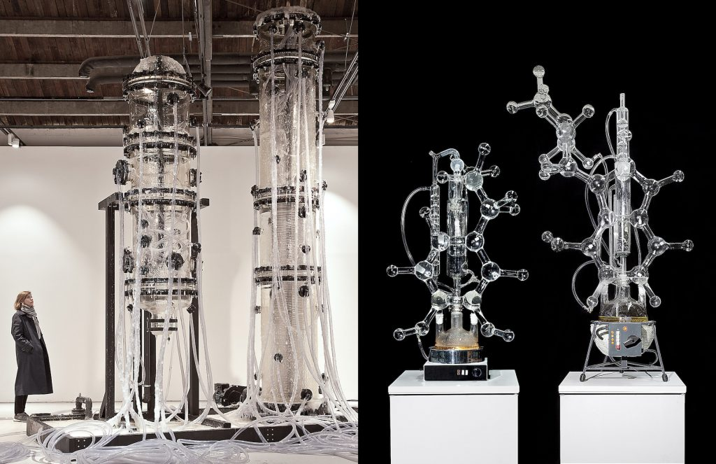 Left: A person looking up at very large stacked chemistry-like glassware, fitted with dangling plastic tubes. Right: Chemistry-like glassware in the shape of molecular structures sitting on white pedastals in front of a black background.