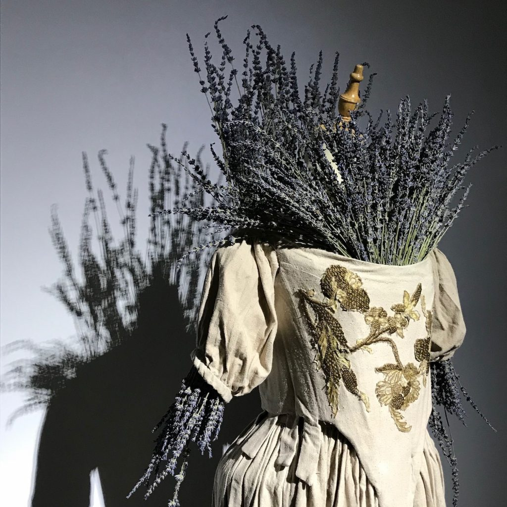 A 1665-style cream-colored dress with a golden floral design stitched onto the bodice. The top and arms of the dress are stuffed with large bunches of lavendar.