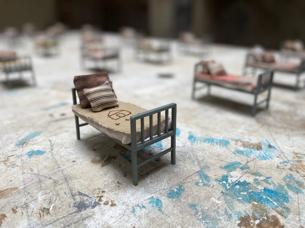 Many miniature beds with a blanket and pillow each are lined up on a worn-looking table in a room with crumbling walls.