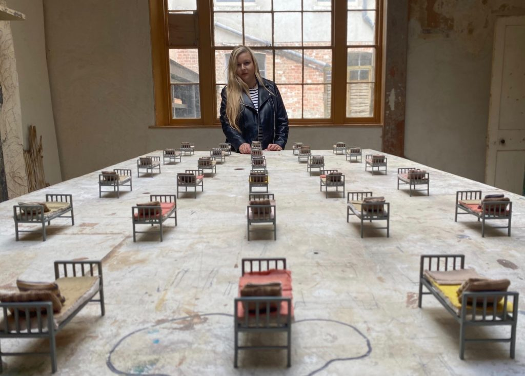 Many miniature beds with a blanket and pillow each are lined up on a worn-looking table in a room with crumbling walls. The artist stands at the end of the table.