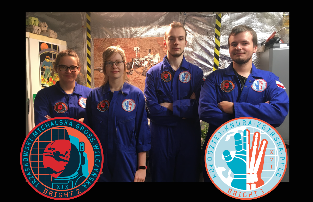 A photograph of four people wearing blue coveralls, each with two patches, one on either side of the chest. At the forefront of the photo are closeups of the graphics on the patches: A planetary body on one and a hand (half glove half skeleton) on the other.