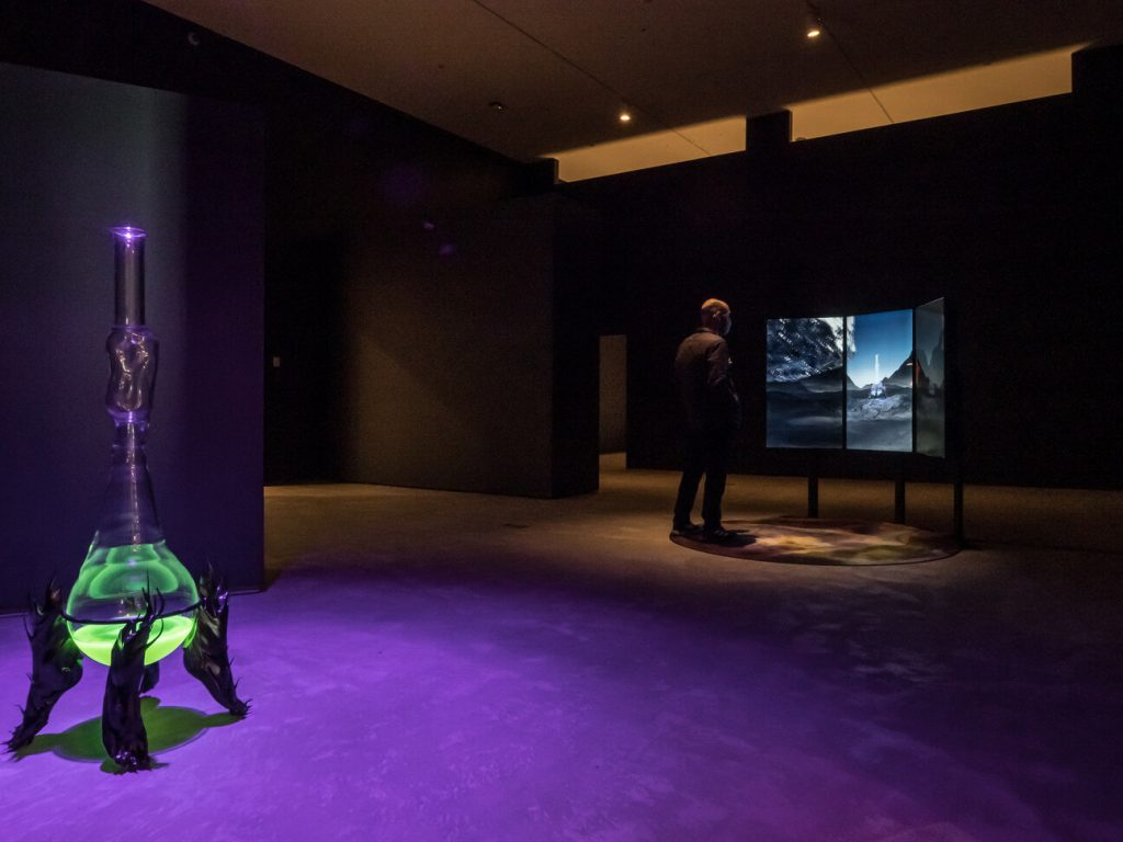 A large, dimly lit room. On the left is a large vessel holding a glowing green substance. On the right is a man looking at a series of three screens.