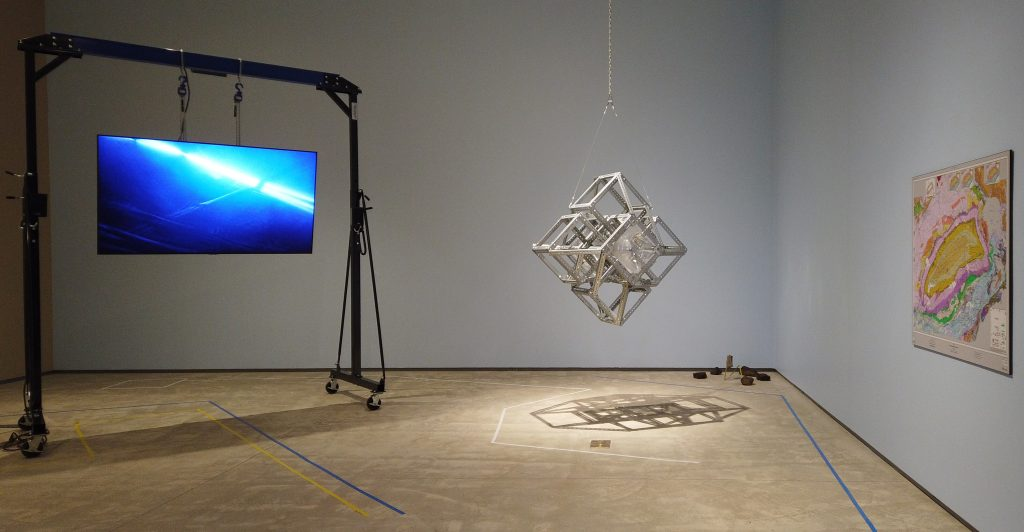 The corner of a large room. From a tall frame hangs a screen showing a blue background with a bright blue stripe of light. From the ceiling hangs a sculpture that looks like a series of metal geometric cube-like shapes. On the wall is a colourful graphic print.