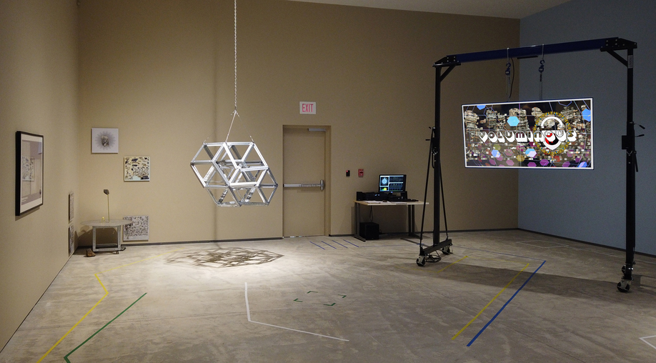 """A large room showcasing a metallic geometric sculpture, that looks like a series of cubes, hanging from the ceiling. There is also, hanging from a high frame, a screen that reads """"voluminous""""."""