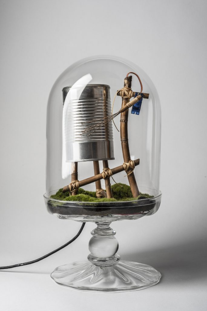 Clear glass terrarium containing a wooden mechanism that rakes metal wires across a tin can, sitting on top of moss