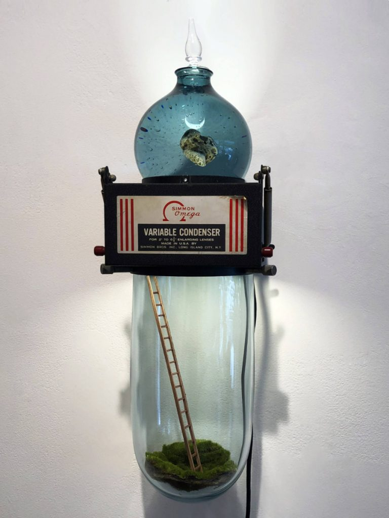 Three objects stacked on top of one another: a blue glass container holding a meteorite, a darkroom condensor, and a clear glass terrarium containing moss and a small wooden ladder