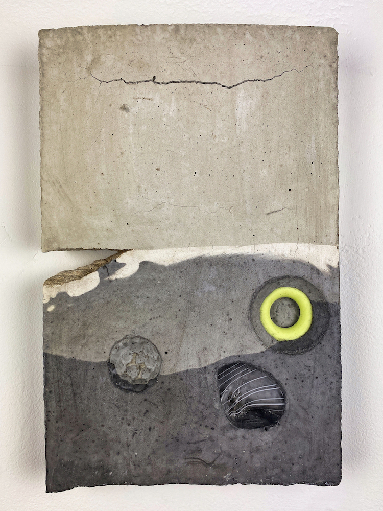 A grey rectangular slab of concrete embedded with grey stones and a ring of yellow material