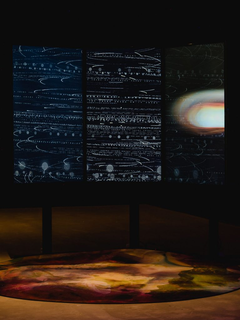 Three large screens showing a photomontage: a dark background with white dots and lines and what looks like a lens flare on the right.