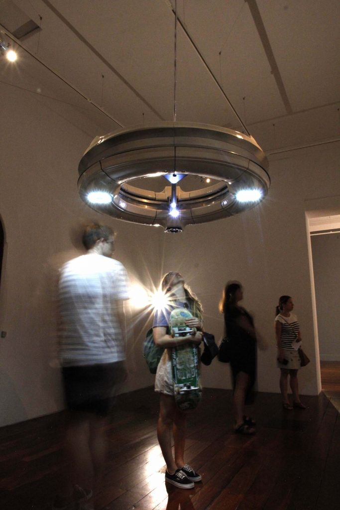 A woman stands in a gallery looking up at Bricolage, a ring-like incubator hanging from the ceiling.