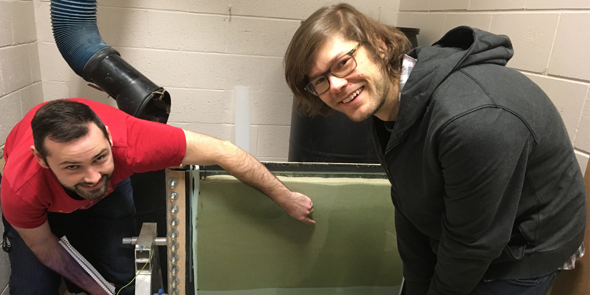 Photo of student showing Owen a sand apparatus